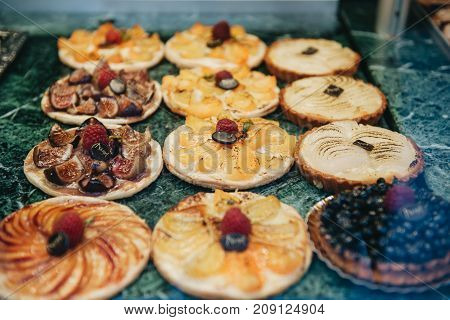 Savory various fruit date pear peach and blackberry tartelette desserts displayed in a French patisserie vitrine