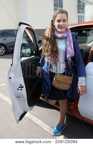 Girl with bag stands near car with opened door and smiles near building