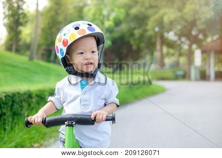 Cute little Asian 1 years / 18 months old baby boy child wearing safety helmet learning to ride first balance bike in sunny summer day kid playing & cycling at park Child first experience concept