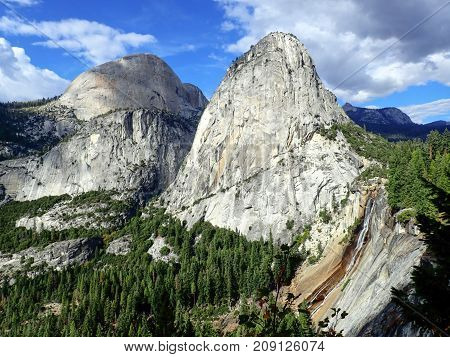 Vast View of Sierra Nevada Mountains of California with Nevada Falls in Foreground Under Blue Sky