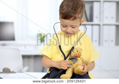 Happy little patient after health exam. Little doctor examining a toy bear with stethoscop