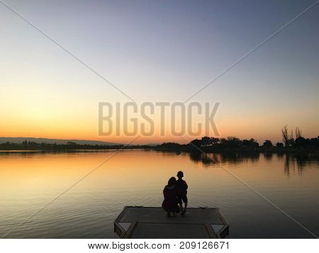 Mom and son on a peaceful lake enjoying nature's twilight.