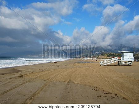 Morning After Storm at California Beach with Sand Sea and Lifeguard Tower Under Puffy Clouds and Blue Sky