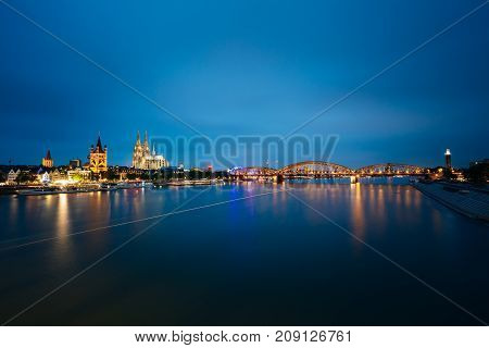 Night View Of St. Martin Church And Cologne Cathedral And Hohenzollern Bridge, Germany. Europe. World Heritage - a Roman Catholic Gothic Cathedral. Panorama Panoramic View Night Cityscape
