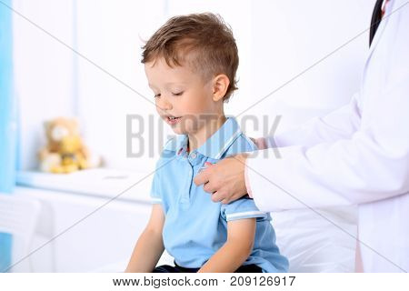 Happy little boy having fun while is being examine by doctor by stethoscope. Health care, insurance and help concept.