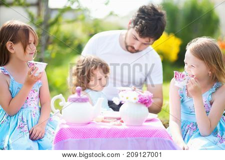 Father playing tea party with his three adorable daughters. Having many children single father. Loving and caring father. Single parent. Beautiful decorated tea party outdoors at the backyard. male babysitter sitter childminder sitter-in.