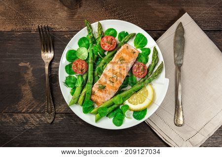 An overhead photo of a plate of grilled salmon with green asparagus, cherry tomatoes, corn salad, and a slice of lemon, a healthy diet dish shot from above on a rustic texture with a place for text