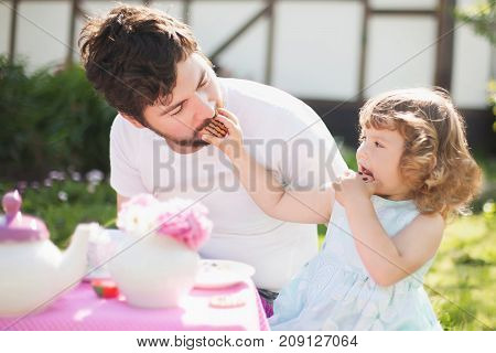 Single father and his adorable toddler princess girl outdoors playing tea party. Little daughter feeding her father with cookies.