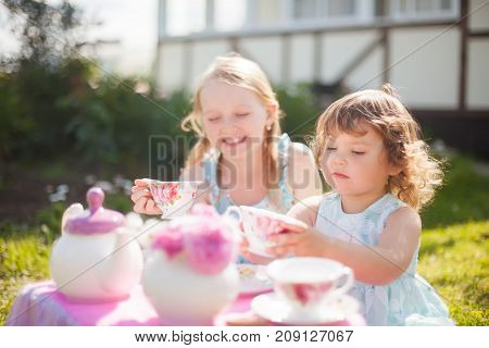 Adorable little sisters dressed like princesses playing tea party. Beautiful decorated tea party outdoors at the backyard.