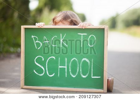 Adorable little girl hiding behind the chalkboard don't want back to school. Have promlems with schoolmates or teathers. Stressed outsider kid. Teathers pressure consept. Negative feelings fear of school.