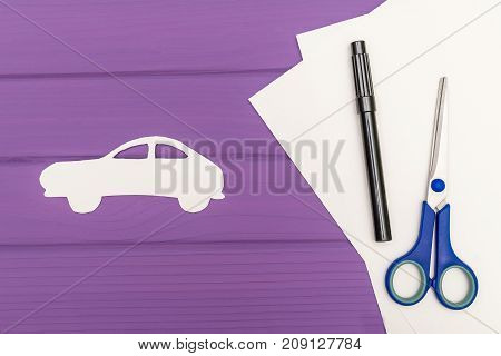 The silhouettes cut out of paper of car, scissors and marker near on a white sheet of paper on purple wooden background, car insurance concept