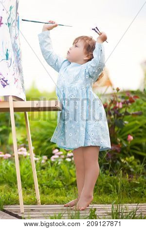 Adorable Toddler Girl Painting On The Easel In The Garden