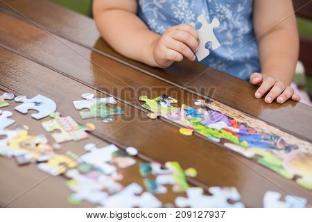 Little kids hands with jigsaw puzzle on a table. Early education concept.