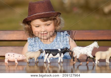 Cute toddler girl playing with farm animal figures outdoors. Summer leisure. childhood on countryside. Child learning farm animals. Early education and developement. Role-playing with plastic animals.