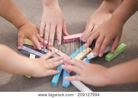 Closeup photo of child hands with piece of chalk summer and childhood concept sunny day active leisure having fun.