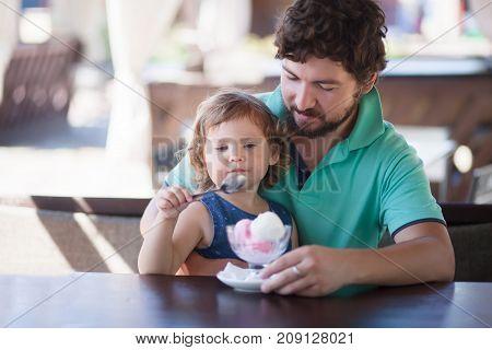 Father feeding llittle girl with ice cream indoors. Family lifestyle.