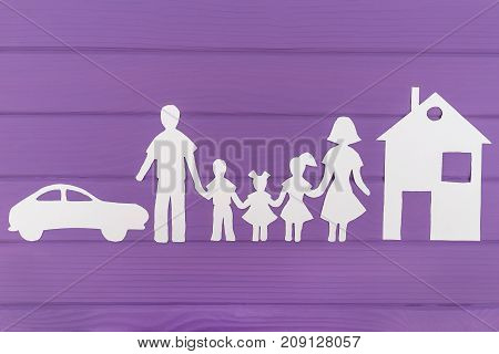 The silhouettes cut out of paper of man and woman with two girls and boy house and car near on purple wooden background. Concept of family protection