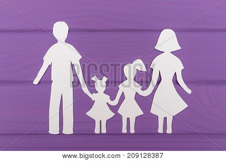 The silhouettes cut out of paper of man and woman with two girls on purple wooden background. Concept of family love