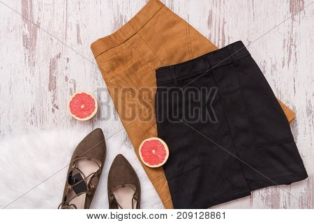 Brown and black suede skirt brown shoes cut grapefruit halves.Fashion concept.