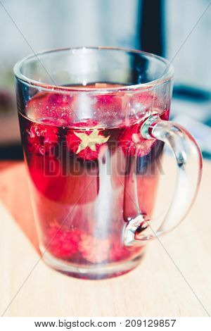 Raspberry tea. Red fruit tea, hot energy drink in glass mug. Teatime, pastime, cozy atmosphere in home, cafe, cafeteria in cold weather. 5 o'clock. Traditional black tea with herbs and berries.