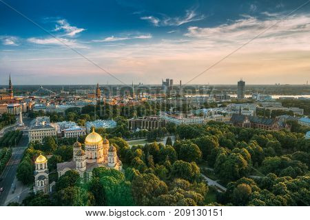 Riga, Latvia. Riga Cityscape. Top View Of Riga Nativity Of Christ Cathedral - Famous Church And Landmark In Summer Evening. Aerial View At Sunset Time. Golden Yellow Domes.
