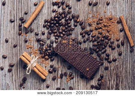 Wafers in chocolate on a wooden table with coffee beans and cocoa powder. View from above