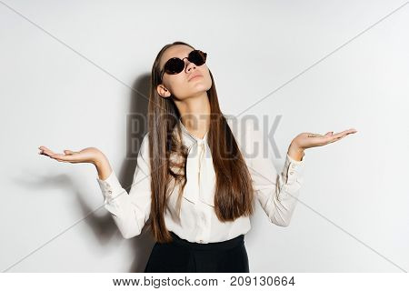 a girl with long hair and a white blouse and with round glasses raises her arms to the sides and looks somewhere up. Isolated on white background.