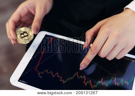 a tablet in the hands of a girl. gold coin. bitcoins. Statistics of incomes. Schedule. Electronic money. Crypto currency