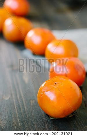 Persimmon snake on wooden surface made from ripe persimmons.