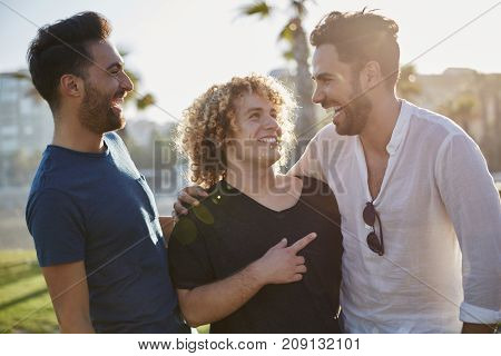 Three Male Friends Talking Together Outside Laughing