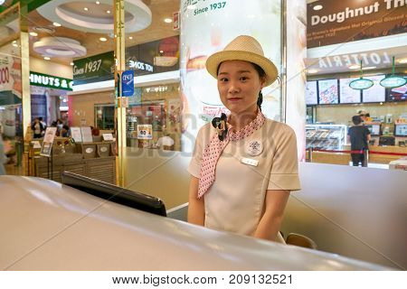 BUSAN, SOUTH KOREA - MAY 28, 2017: indoor portrait of staff at Lotte Department Store information desk.