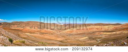 Panoramic of a road in desert with mountains and blue sky in Argentina