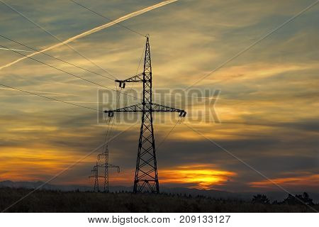 electricity pillars at sunset silhouettes on beautiful orange sky