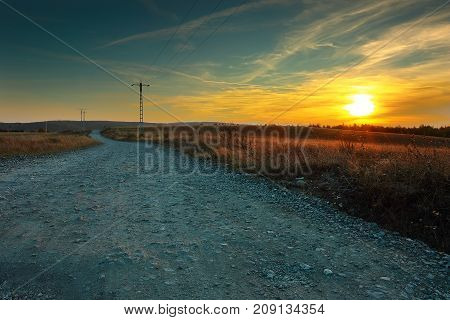 view of a rural road at sunset beautiful orange colors at the horizon