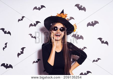 Halloween Party girl. Happy Halloween Sexy Witch with a black hat. Beautiful young smiling woman in witches hat and costume Isolated on white background
