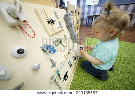 Little girl plays on soft carpet with wooden busy board in modern kindergarten