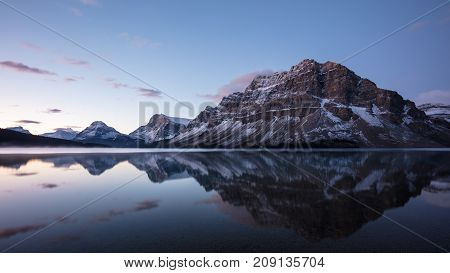 Canadian Rockies reflected in Bow Lake before sunrise in Banff National Park, Alberta