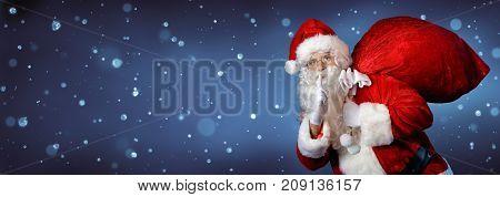 Santa Claus Carrying Big Bag In Night