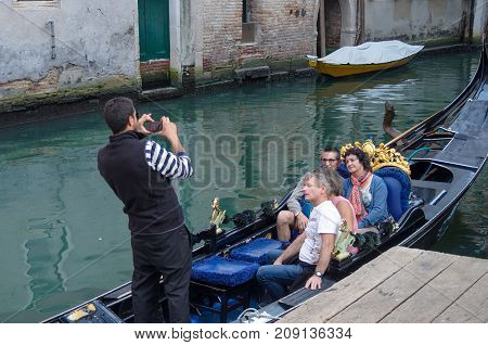 VENICE ITALY - SEPTEMBER 29 2017: Gondola with tourists on a canal in Venice. Gondolier is taking pictures of tourists in the gondola.