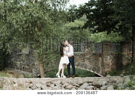 beautiful newlyweds kissing on the bridge in the park
