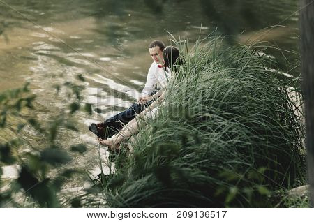 Beautiful couple sit near a lake in the park