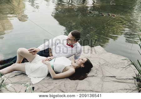 newlyweds lie on stone near lake with ducks in park
