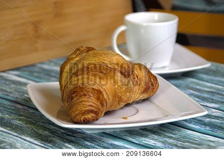 Traditional French butcher croissant on a plate. Cup in the background.