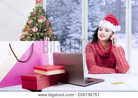 Beautiful woman wearing a Santa hat and sweater buying Christmas gifts online while making a phone call with a laptop computer on desk at home