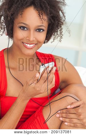 A beautiful mixed race African American girl or young woman wearing a red dress listening to music on mp3 player and headphones