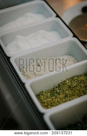White containers whith the spices for making pizza