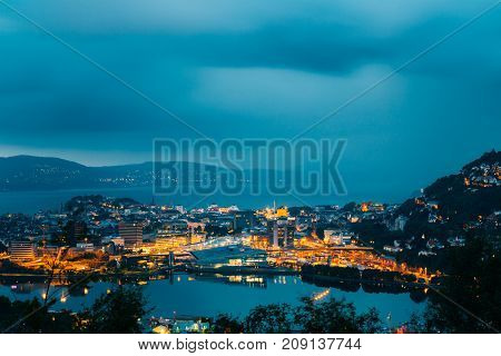 Bergen, Norway. Aerial View Cityscape Of Bergen And Harbor From Mountain Top In Blue Hour. City In Summer Evening Or Night Illuminations Lighting.