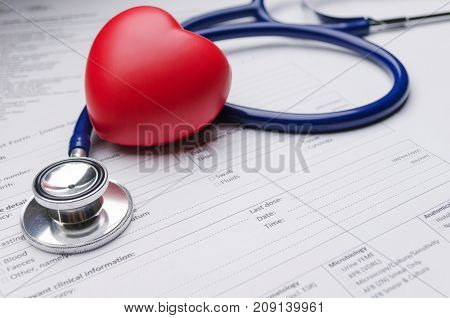 close up of red heart stethoscope and medical form on desk heart attack heart disease medical diagnosis medical report record and history patient concept selective soft focus