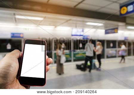 hand using mobile phone with blank screen over blurred view of people waiting subway at train station people transportation internet social media network connection and technology concept