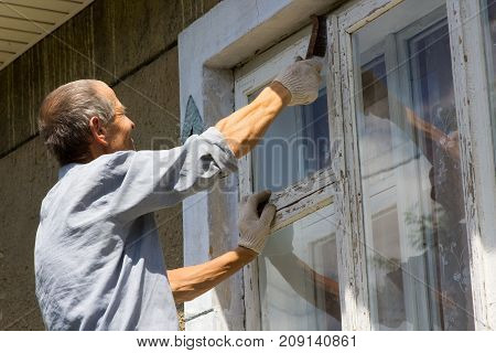grandfather cleans a window with paint in the house
